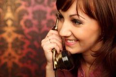 Portrait of girl talking on retro phone stock image