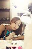 Portrait of a girl tattoo master during creation tattoo on a man`s hand. Royalty Free Stock Images