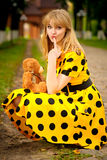 Portrait of girl with teddy bear. Young woman in yellow dress holds toy bear cub in city park Royalty Free Stock Image