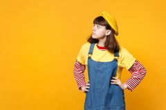Portrait of girl teenager in french beret, denim sundress standing with arms akimbo, looking aside isolated on yellow. Wall background. People sincere emotions stock photography