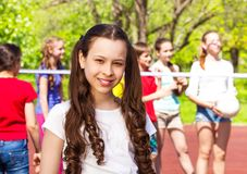 Portrait of girl with teens playing volleyball Stock Photography