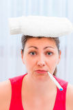 Portrait of a girl with a thermometer in her mouth and hot water Royalty Free Stock Photos