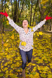 Portrait of a girl throws herself maple leaves. Girl throws in the sky bunch of autumn leaves Royalty Free Stock Image