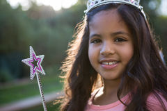 Portrait of girl in tiara and wand. Portrait of happy girl in tiara and wand at the garden royalty free stock photography