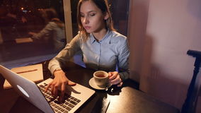 The portrait of the girl typing on the laptop and drinking coffee. 4K. The portrait of the girl typing on the laptop and drinking coffee stock video footage