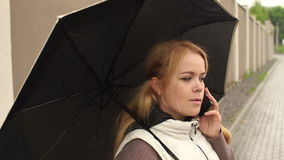 Portrait of a girl under an umbrella with a phone. Girl with long blond hair under an umbrella talking on the phone in a rainy day in the street stock video footage