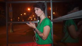 Girl uses a smartphone at a bus stop at night, the bus will arrive stock video footage