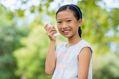 Portrait of girl using an asthma inhaler in the park Royalty Free Stock Photos