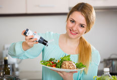 Portrait of girl with vegetable salad and balsamico. Pretty housewife holding plate with vegetable salad and balsamico royalty free stock photo