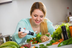 Portrait of girl with vegetable salad and balsamico. Pretty housewife holding plate with vegetable salad and balsamico stock photos