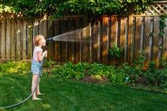 Little girl watering green plants on backyard stock photos