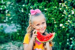 Portrait of a girl with a watermelon in nature. The child holds a piece of watermelon in his hands royalty free stock photos