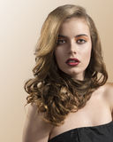 Portrait of girl with wavy hair, she looks in to t. Pretty girl with wavy hair and red lipstick, she is in front of the camera and looks in to the lens Royalty Free Stock Images