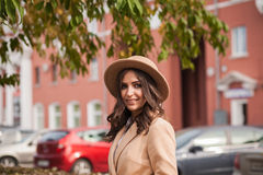 Portrait of a girl wearing  hat and coat against the backdrop  urban landscape  machines Stock Photos