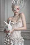 Portrait of a girl in a whight costume holding a white bunny. In studio stock photos