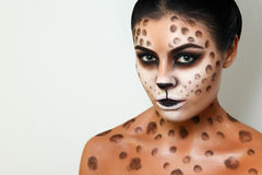 Portrait of a girl on a white background. . face art. body art. hairstyle. black hair. wild cat. black hair. Drawing on the body. female emotions. creative make Stock Photography