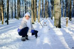 Portrait of a girl in white hat and scarf outside sitting near funny snowman. Blue sky and frosty trees on background. Stock Images