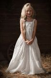 Portrait of a girl in a white sundress on the hay in the barn Royalty Free Stock Photography