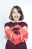 Portrait of a girl who holds a gift to the viewer. Royalty Free Stock Photography