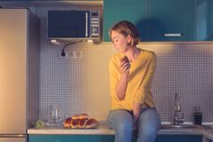 Portrait of a girl who looks with pleasure at the pastries sitting on the table in the kitchen royalty free stock photography