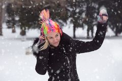 Portrait of a girl who plays and wears clown colored wig and headphones on snowy day. Winter concept stock photography