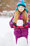 Portrait of girl who stands behind barrier made from snow blocks Royalty Free Stock Photo