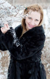 Portrait of a girl in winter. Portrait of young blond woman near the bush sprinkled with snow in the winter holding a branch Royalty Free Stock Photography