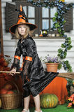 Portrait of girl in witch costume. Charming little witch with hat Stock Image