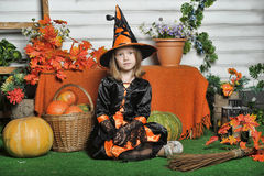 Portrait of girl in witch costume. Charming little witch with hat Stock Images