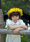 Portrait of the girl in a wreath. From dandelions at a fencing Stock Photo