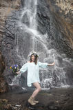 Portrait of a girl with a wreath on her head and a bouquet of flowers in her hands against a waterfall Royalty Free Stock Photography