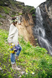 Portrait of a girl with a wreath on her head and a bouquet of flowers in her hands against a waterfall Stock Images