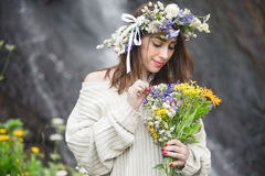 Portrait of a girl with a wreath on her head and a bouquet of flowers in her hands against a waterfall Stock Photography