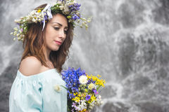 Portrait of a girl with a wreath on her head and a bouquet of flowers in her hands against a waterfall Royalty Free Stock Photo