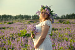Portrait of a girl in a wreath of wild flowers. Pregnant girl in a field with a bouquet of wildflowers and in a wreath Royalty Free Stock Image