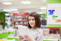 Girl  choosing   books in   bookstore for school. Portrait of   girl  of 8   years  choosing books in   bookstore Royalty Free Stock Images