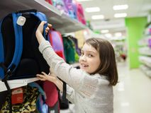 First grader choosing briefcase in store for school. Portrait of girl of 8 years in shop choosing briefcase for school royalty free stock photography