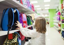 Schoolgirl buying briefcase for school at store. Portrait of girl of 8 years in shop choosing briefcase for .school royalty free stock photo