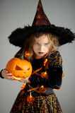 Portrait of the girl 8-9 years in a suit for Halloween. Portrait of the girl of 8-9 years in a suit for Halloween. She represents the evil sorcerer. The girl is stock images