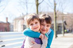 Portrait of girlfriends of 7 and 5 years old. Portrait of two girls on bench in spring day stock images