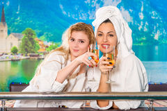 Portrait of girls in white coats. After sauna royalty free stock images