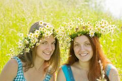 Portrait of girls in wreaths. Portrait of girls in camomile wreaths against nature royalty free stock images