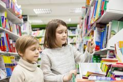 Girls reading books at store. Portrait of girls of 8 and 6 years in shop choosing books royalty free stock photo