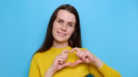 Portrait of glad beautiful young woman shows heart gesture over chest, being passionate, express love to close person