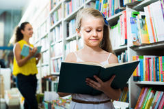 Portrait of glad girl in school age taking book Stock Photo