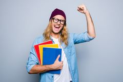 Portrait of glad guy raising his hand with fist having good mood. Celebrating victory holding three colorful copy books standing over grey background. Victory Royalty Free Stock Photography