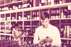 Portrait of glad male customer taking bottle of wine in store Royalty Free Stock Image