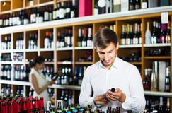 Portrait of glad male customer taking bottle of wine in store Stock Photos