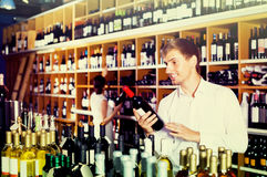 Portrait of glad male customer taking bottle of wine in store. Portrait of young american glad male customer taking bottle of wine in store Stock Images