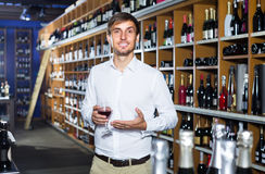 Portrait of glad male customer tasting wine before purchasing it. Portrait of young glad male customer tasting wine before purchasing it in wine store Royalty Free Stock Photos